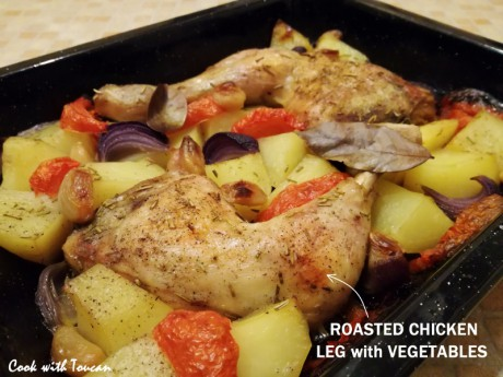 Roasted chicken legs with potatoes, tomatoes and red onion